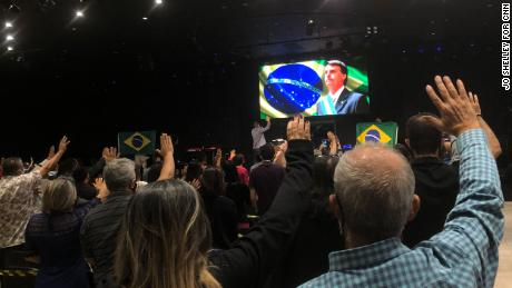 The congregation at Nucléo de Fé evangelical church prays for President Jair Bolsonaro.
