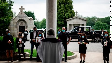 Fabian Arias (center), a Lutheran pastor with Saint Peter's Church in Manhattan, leads a funeral with the family of Francia Nelly, a woman from Ecuador who died of complications related to Covid-19, at the St. John Cemetery in Queens on June 5, 2020, in New York City.
