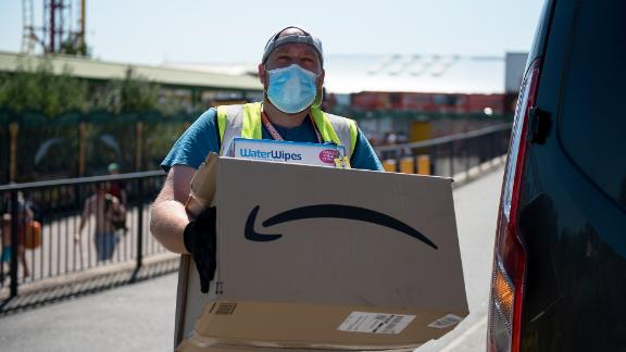 An Amazon delivery person wearing a face mask delivers a parcel along the promenade on June 25, 2020 in Southend-on-Sea, England. The UK is experiencing a summer heatwave, with temperatures in many parts of the country expected to rise above 30C and weather warnings in place for thunderstorms at the end of the week. (Photo by John Keeble/Getty Images)
