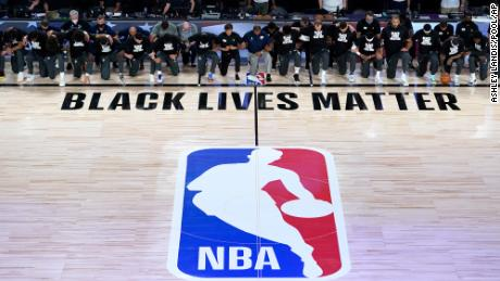 Coaches, referees and members of the New Orleans Pelicans and Utah Jazz kneel together at the Black Lives Matter logo during the national anthem before the NBA basketball game on Thursday in Lake Buena Vista, Florida.