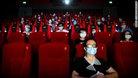 """People wearing face masks to protect against the coronavirus sit spaced apart as they watch the film """"Dolittle"""" at a movie theater in Beijing  (AP Photo/Mark Schiefelbein)"""