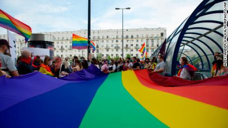 LGBTQ demonstrators hold a huge rainbow flag during a protest on June 20 in Warsaw, Poland.