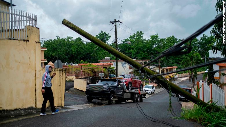 A man guides a tow truck under a downed power line pole after Tropical Storm Isaias affected the area in Mayaguez, Puerto Rico, on Thursday.