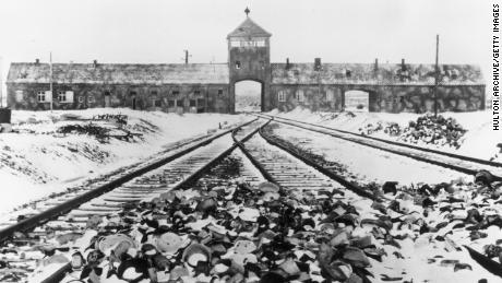 Snow-covered personal effects of those deported to the Auschwitz concentration camp litter the train tracks leading to the camp's entrance, in an image from around 1945.