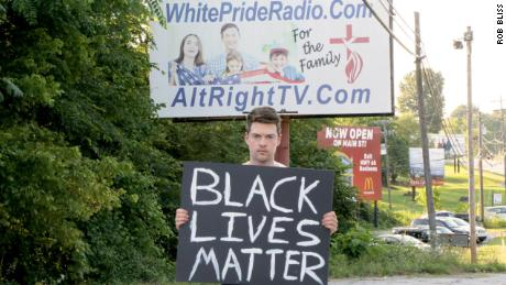 Rob Bliss standing in front of a billboard in Harrison, Arkansas, with his Black Lives Matter sign.