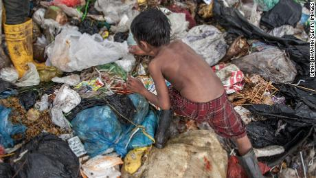 Growing up amid violence or poverty can be linked to accelerated aging, a new review of studies shows. A young boy searches for plastic in the Anlong Pi landfill in Siem Reap, Cambodia.