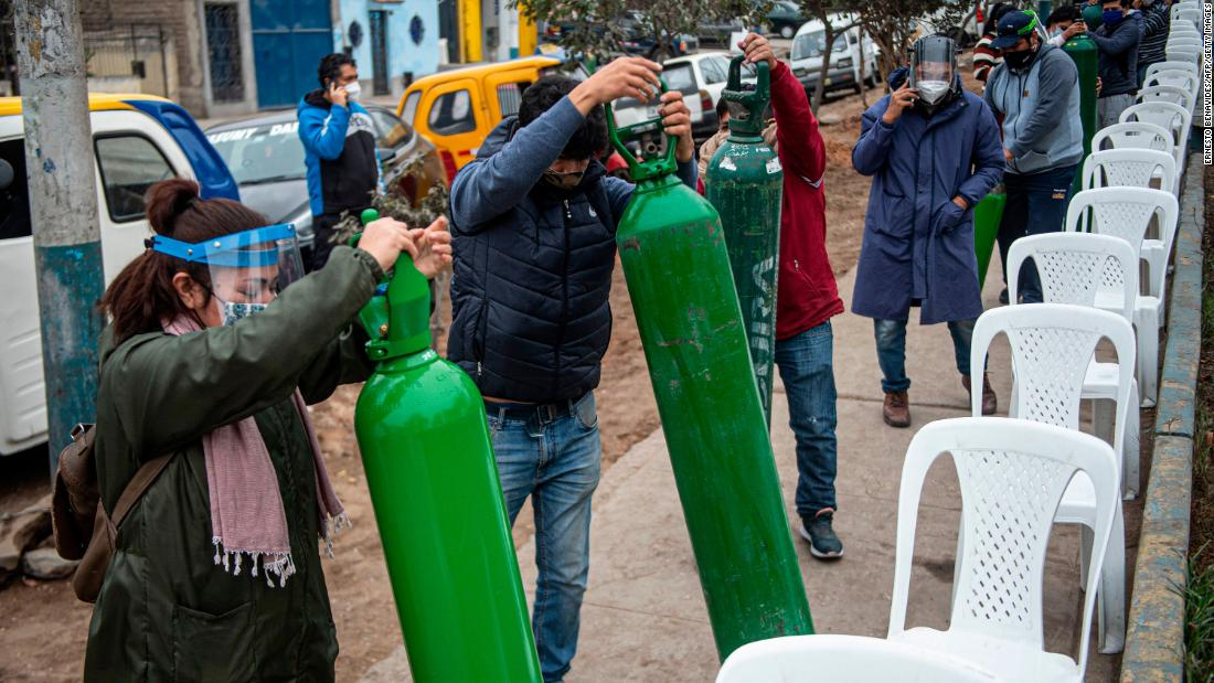Relatives of Covid-19 patients line up to recharge oxygen cylinders in Villa Maria del Triunfo, Peru, on July 29.