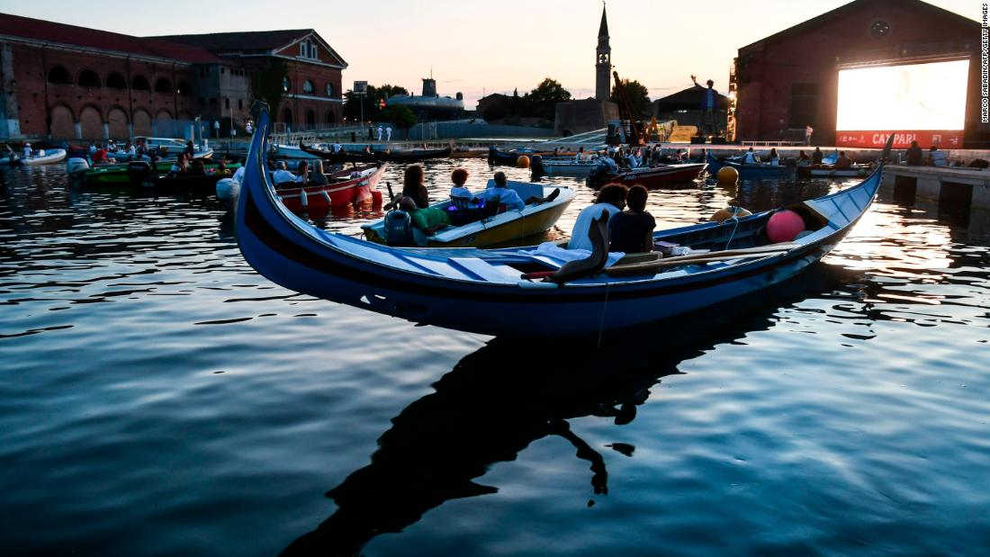 "People watch the film ""The Prestige"" from a gondola boat in Venice, Italy, on July 28. Around the world, many films are being shown outside so that people can practice social distancing."