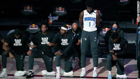 Orlando Magic forward Jonathan Isaac stands as others kneel before the start of the game between the Brooklyn Nets and the Magic on Friday.