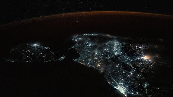 Sri Lanka and the brightly lit southern tip of India are shown in this photograph from the International Space Station on July 24. A starry sky and an atmospheric glow frame the Earth's horizon.
