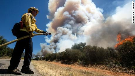 A firefighter readies a hose at the Apple Fire in Cherry Valley, Calif., Saturday, Aug. 1, 2020.