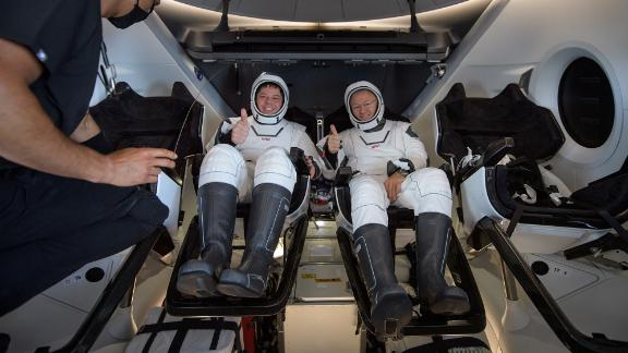 Behnken and Hurley give a thumbs-up before being extracted from the Crew Dragon spacecraft.