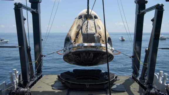 The Crew Dragon spacecraft is lifted onto a recovery ship shortly after splashdown.