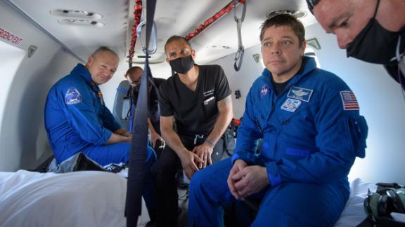 Hurley, left, and Behnken, second from right, ride in a helicopter after returning from space.