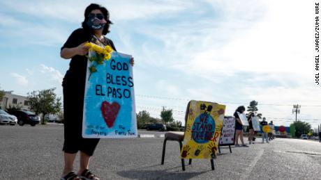Anna Perez, 53, holds a sign during a transit vigil in El Paso, Texas, to honor the 23 victims of the Walmart shootout on Saturday.