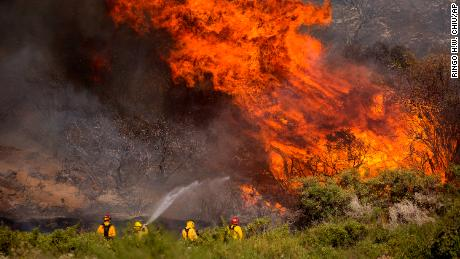 Firefighters work against the Apple Fire near Banning, California, on Sunday