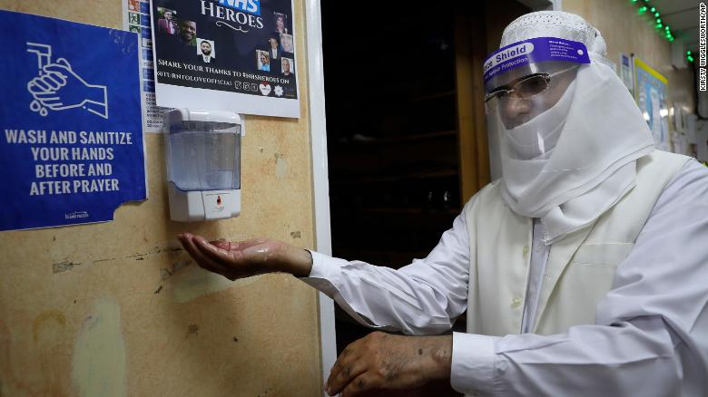 A volunteer uses hand sanitizer as he enters Minhaj-ul-Quran Mosque in London on July 31.