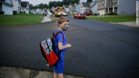 CORRECTS LAST NAME TO ADAMUS, NOT ADAMS - Paul Adamus, 7, waits at the bus stop for the first day of school on Monday, Aug. 3, 2020, in Dallas, Ga. Neighboring states arrived at differing conclusions on who's in charge of the reopening of schools. The differences in philosophy underscore some of the difficulties facing states as they grapple with how to proceed amid growing coronavirus infections in numerous states. (AP Photo/Brynn Anderson)
