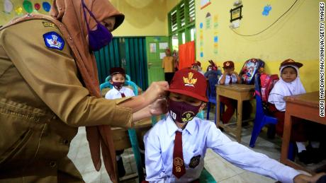 A teacher fixes a face mask for an elementary school student on July 13 in West Sumatra, Indonesia.