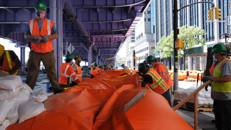 New York City workers erect flood barriers to protect against an expected storm surge.