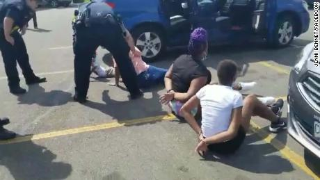 A Facebook video shows the children on the ground in a parking lot, surrounded by police.