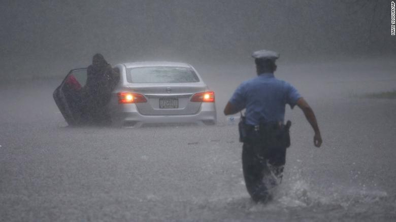 A Philadelphia police officer rushes to help a stranded driver Tuesday during Tropical Storm Isaias.