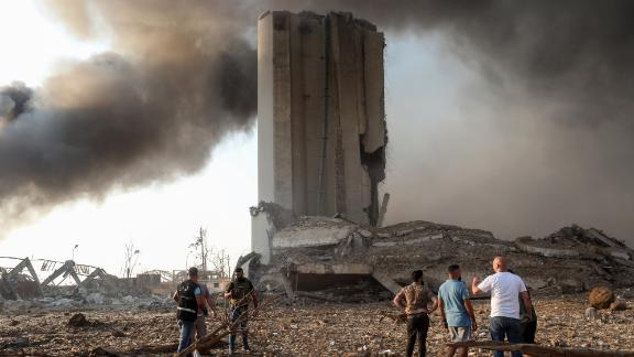 People gather by damaged buildings after the blast.