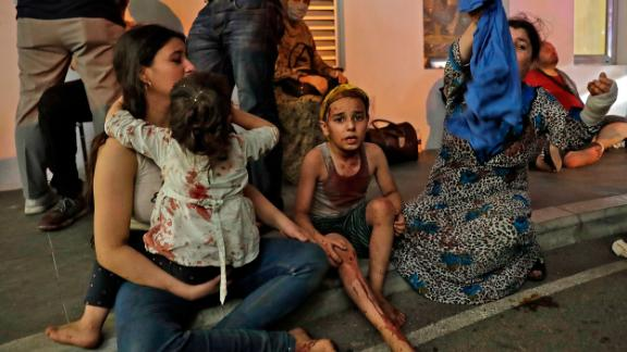 Wounded people wait to received help outside a hospital. Emergency wards have been inundated.