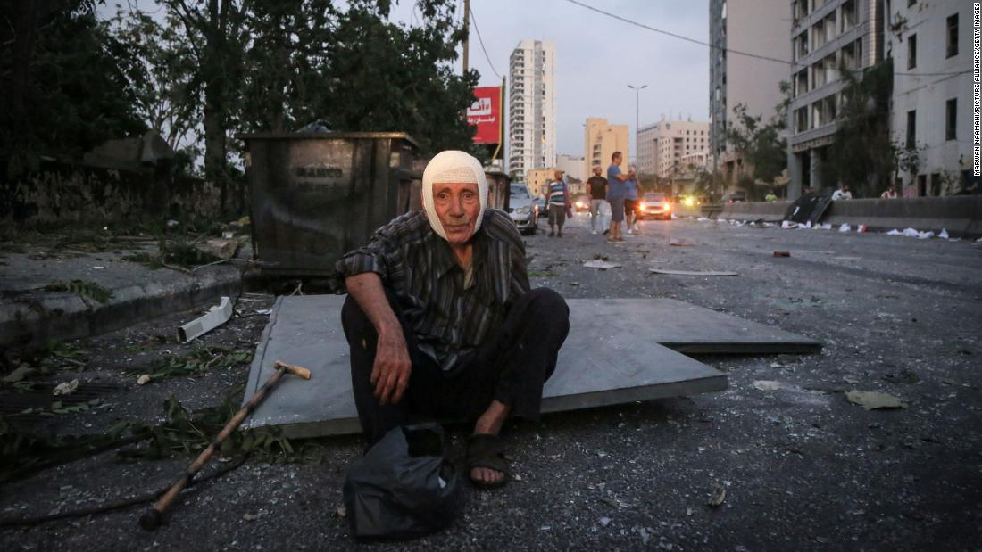 A man sits near the site of the blast.