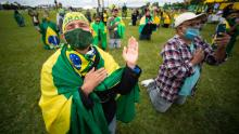 Supporters of Brazilian President Jair Bolsonaro pray during a motorcade and protest against the National Congress and the Supreme Court over lockdown measures amidst on the coronavirus (COVID-19) pandemic in front the National Congress on May 09, 2020 in Brasilia.