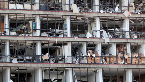 Debris hangs from a damaged facade.