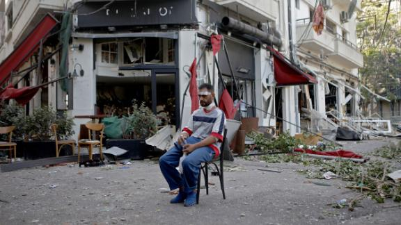 An injured man sits next to a restaurant in the Mar Mikhael neighborhood on Wednesday.