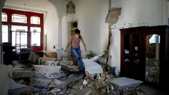 A woman walks over rubble in her apartment on Wednesday.