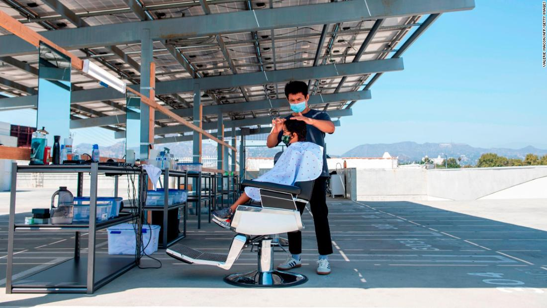 A stylist from Grey Matter LA cuts a client's hair on a rooftop parking lot in Los Angeles on August 4.