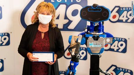 New multimillionaire, Guylaine Desjardins, stands next to the robot that presented her with her winnings.