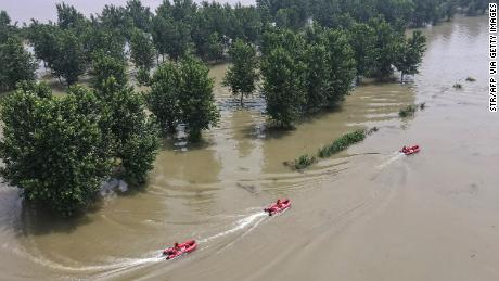 This aerial photo shows firefighters patroling with boats at a flooded area near the Yangtze river in Zhenjiang, in China's eastern Jiangsu province on July 20, 2020. (Photo by STR/AFP via Getty Images)