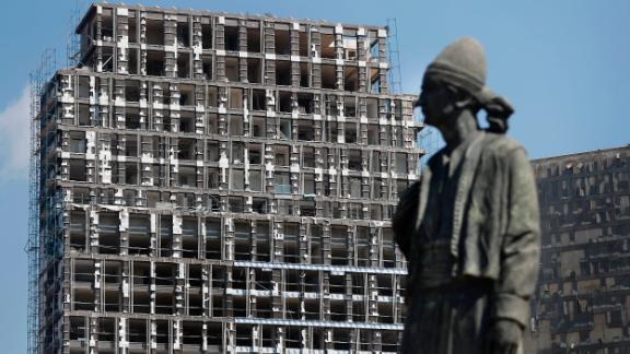 A statue representing the Lebanese expatriate is seen Wednesday in front of a building that was damaged by the explosion.