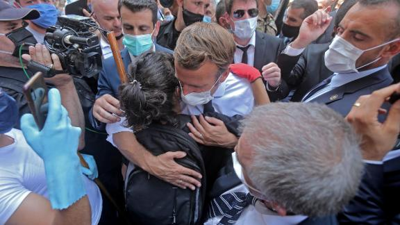 """A person hugs French President Emmanuel Macron during his visit to the Gemmayzeh neighborhood in Beirut on Thursday. Large crowds, chanting """"revolution, revolution,"""" mobbed Macron as he toured the neighborhood. France has sent an aid package to Lebanon that includes two military planes, 55 personnel, 15 tons of equipment and a mobile clinic that's able care for 500 wounded people."""