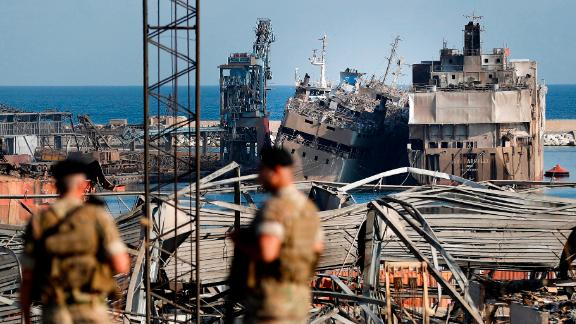 Lebanese soldiers stand guard in front of destroyed ships Thursday.