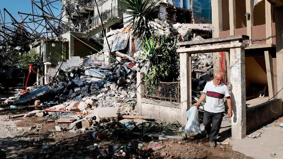 A man carries his belongings as he leaves his destroyed house on Thursday. Hundreds of thousands of people have been displaced.