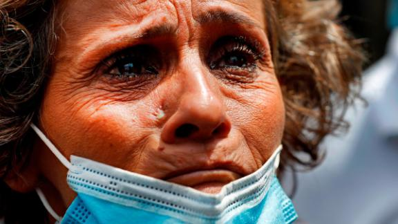 A woman, whose son is said to be missing after Tuesday's explosion, waits outside Beirut's port on Thursday to receive information from rescue teams.