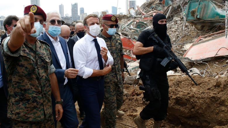 Macron, surrounded by Lebanese servicemen, visits Beirut's devastated port.