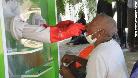A patient takes a coronavirus test at a hospital in Nigeria. Some people are treating the virus at home in Africa because of difficulties getting tested and treated.