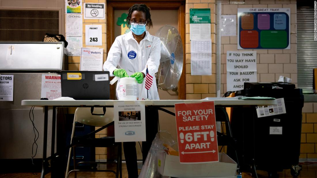 Poll worker Debra Moore sanitizes her workspace during a primary election in Detroit on August 4.