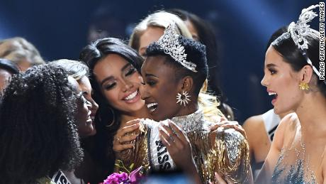 ATLANTA, GEORGIA - DECEMBER 08: (EDITORIAL USE ONLY) Miss Universe 2019 Zozibini Tunzi, of South Africa, is crowned onstage by Miss Universe 2018 Catriona Gray (R, in blue) at the 2019 Miss Universe Pageant at Tyler Perry Studios on December 08, 2019 in Atlanta, Georgia. (Photo by Paras Griffin/Getty Images)