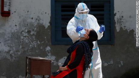 A medic wearing personal protective equipment collects a swab sample in India.