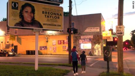People walk by a billboard for Breonna Taylor