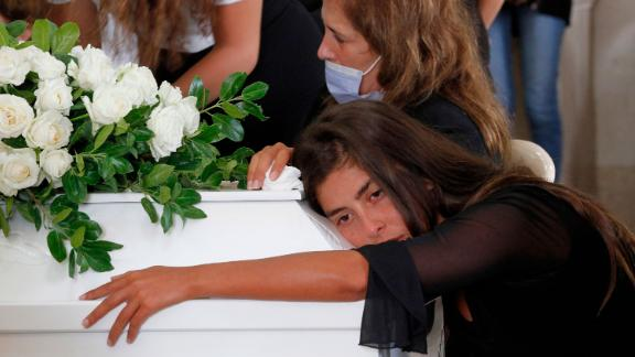 Christelle Helou hugs the coffin of her cousin Nicole in Sarba, Lebanon, on Thursday.