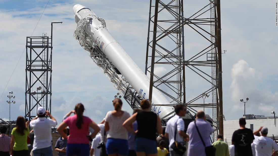 People watch as a SpaceX Falcon 9 rocket attached to the cargo-only Dragon capsule is prepared for a scheduled evening launch on October 7, 2012 in Cape Canaveral, Florida, to bring cargo of clothing, equipment and science experiments to the International Space Station.