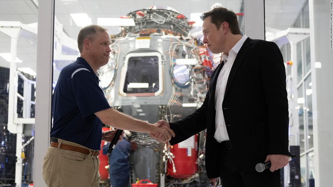 NASA administrator Jim Bridenstine and Elon Musk shake hands in front of Crew Dragon cleanroom at SpaceX Headquarters in Hawthorne, California on October 10, 2019.